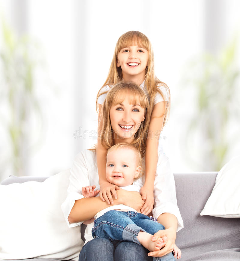 Familia feliz en casa en el sofá. Madre e hija e hijo foto de archivo libre de regalías