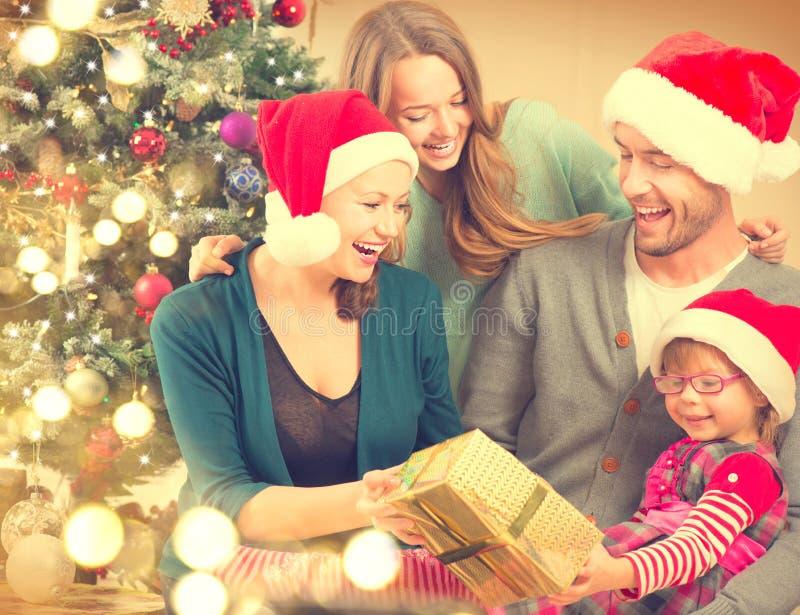 Familia feliz en casa que celebra la Navidad imagen de archivo