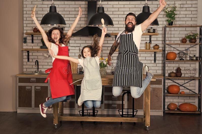 Familia feliz en cocina Disfrutar de ma?ana Padre e hija Ni?a con los padres en delantal Madre y padre imagenes de archivo