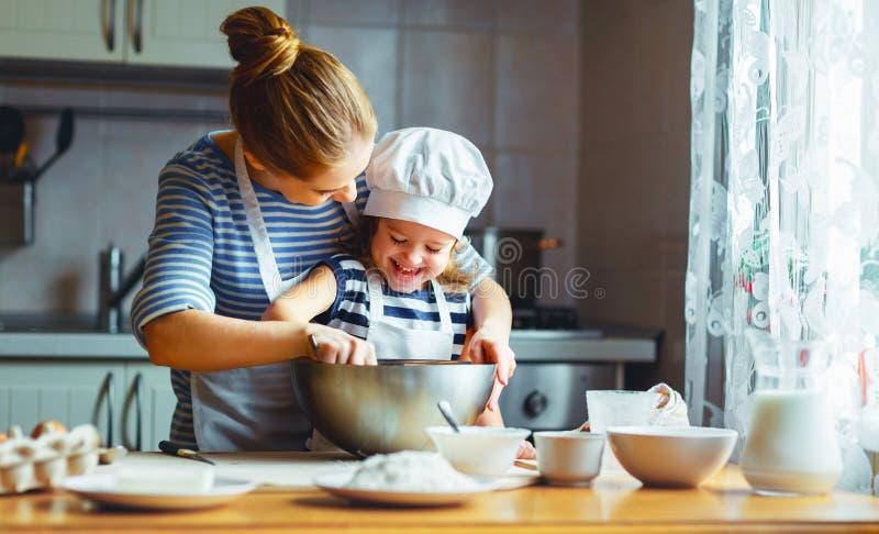 Familia feliz en cocina la madre y el niño que preparan la pasta, cuecen fotografía de archivo
