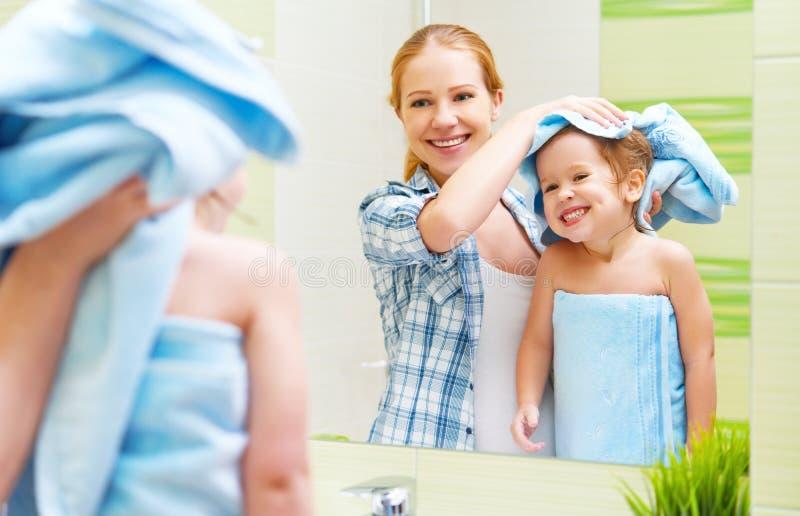 Familia feliz en cuarto de baño madre de un niño con el cabello seco de la toalla imágenes de archivo libres de regalías