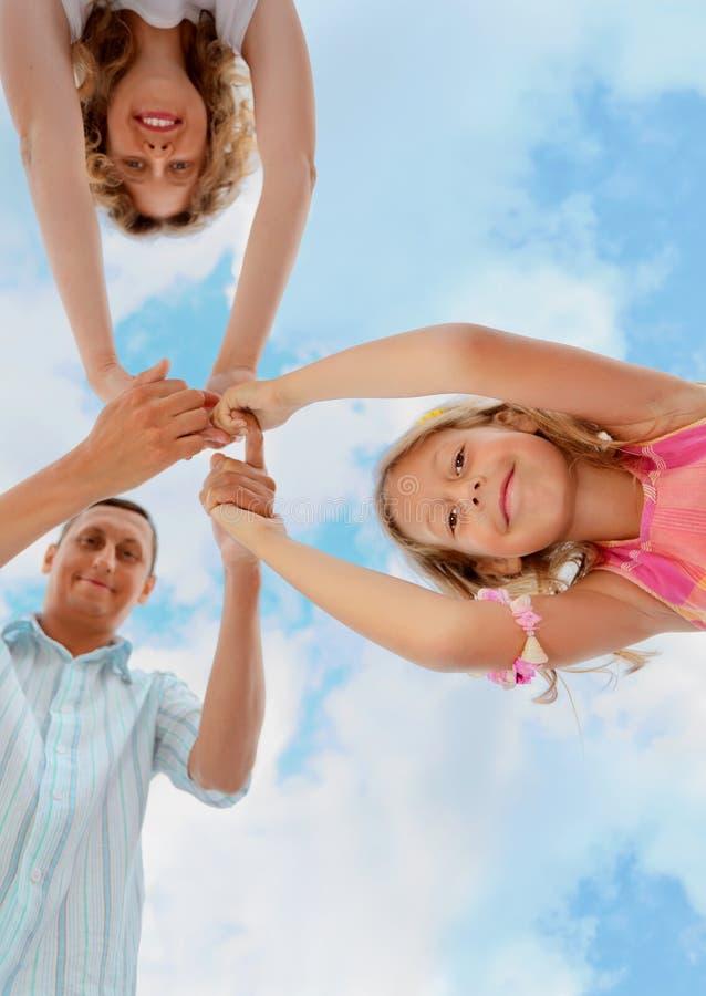 Familia feliz en el cielo, foreshortening de debajo fotos de archivo libres de regalías