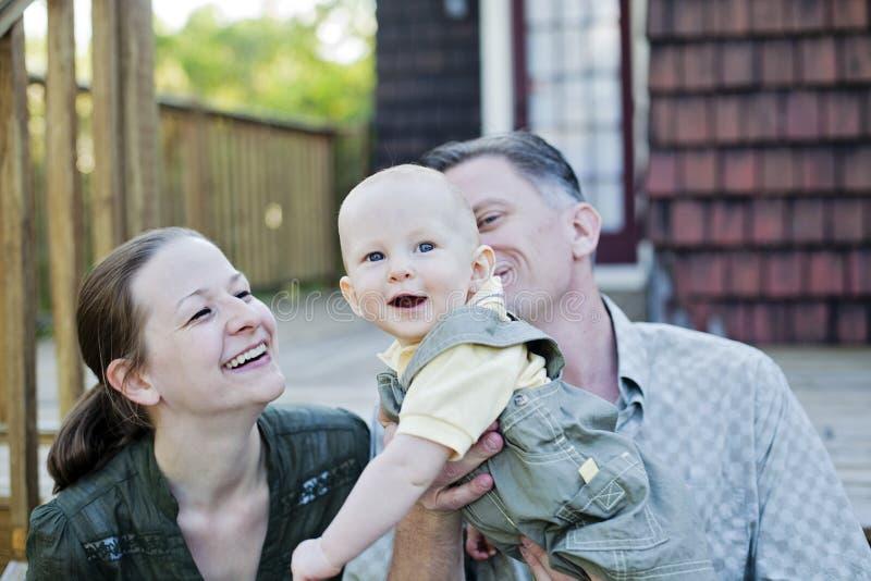 Familia feliz en el pórtico imagen de archivo libre de regalías