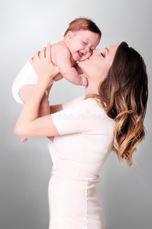 Familia feliz en el país Mime a detener al bebé en dormitorio en wee acogedor fotos de archivo libres de regalías