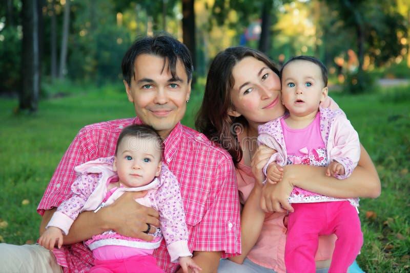 Familia feliz en el parque con el padre, la madre y el bebé de los gemelos - s foto de archivo libre de regalías