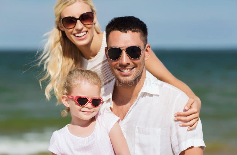Familia feliz en gafas de sol en la playa del verano imágenes de archivo libres de regalías