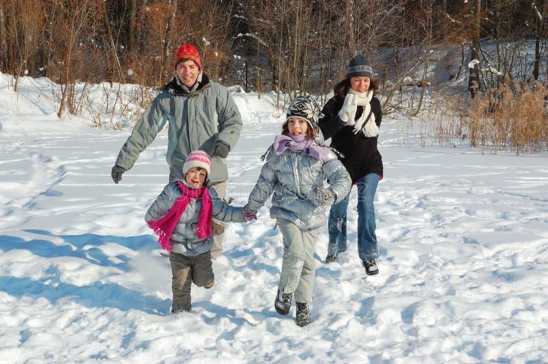 Familia feliz en invierno, divirtiéndose con nieve al aire libre imágenes de archivo libres de regalías