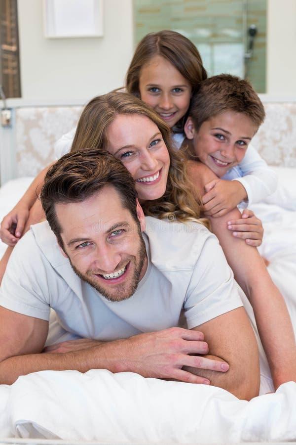 Familia feliz en la cama foto de archivo