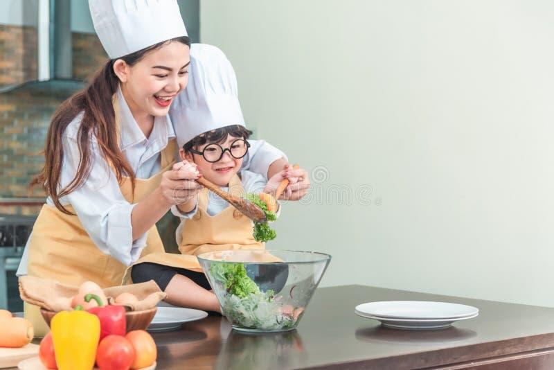 Familia feliz en la cocina hija de la madre y del niño que prepara la pasta, ensalada imágenes de archivo libres de regalías