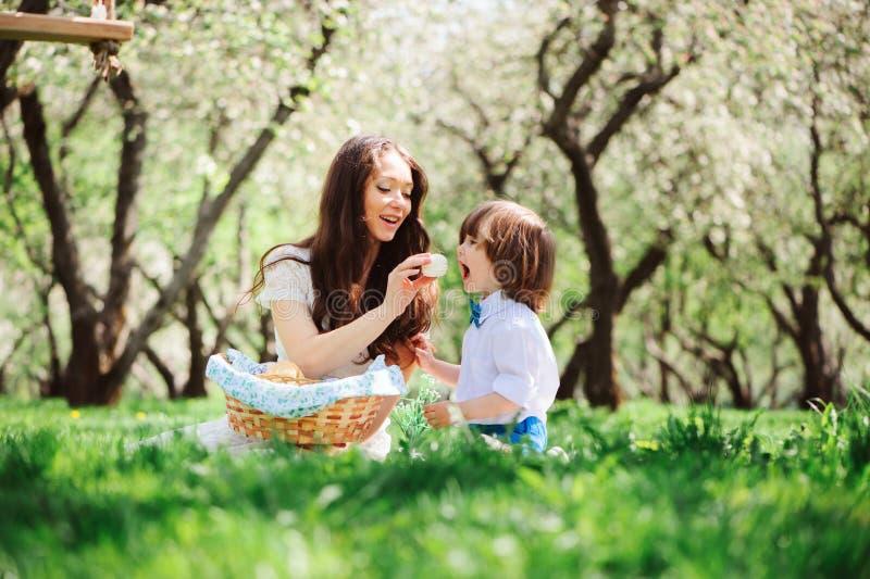 Familia feliz en la comida campestre para el día de madres Hijo de la mamá y del niño que come los dulces al aire libre en primav imagenes de archivo