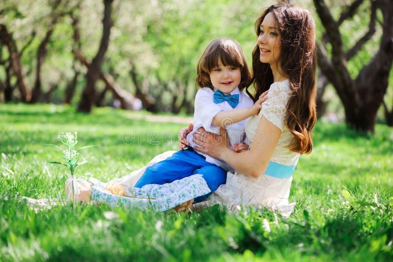 Familia feliz en la comida campestre para el día de madres Hijo de la mamá y del niño que come los dulces al aire libre en primav foto de archivo libre de regalías
