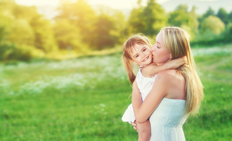 Familia feliz en la madre de la naturaleza que besa a la pequeña hija imagen de archivo