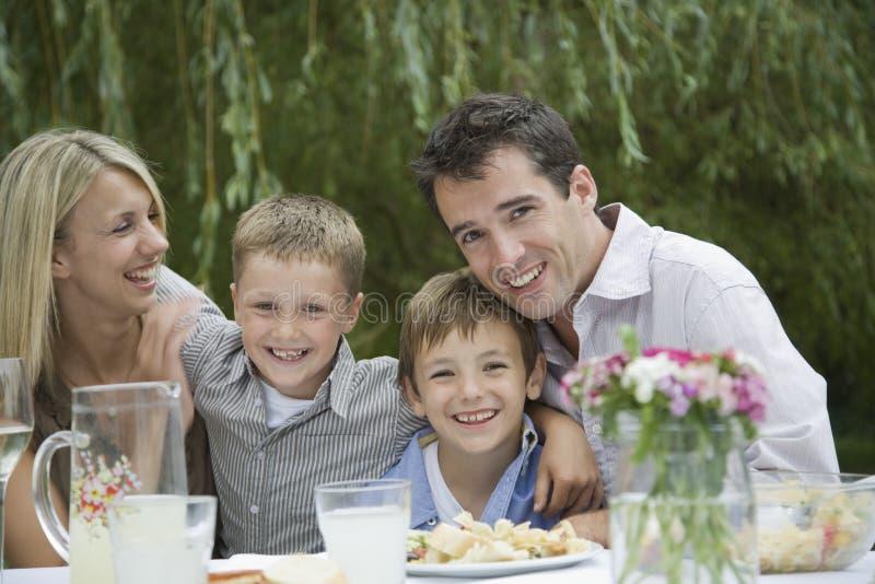 Familia feliz en la mesa de comedor en jardín imagen de archivo