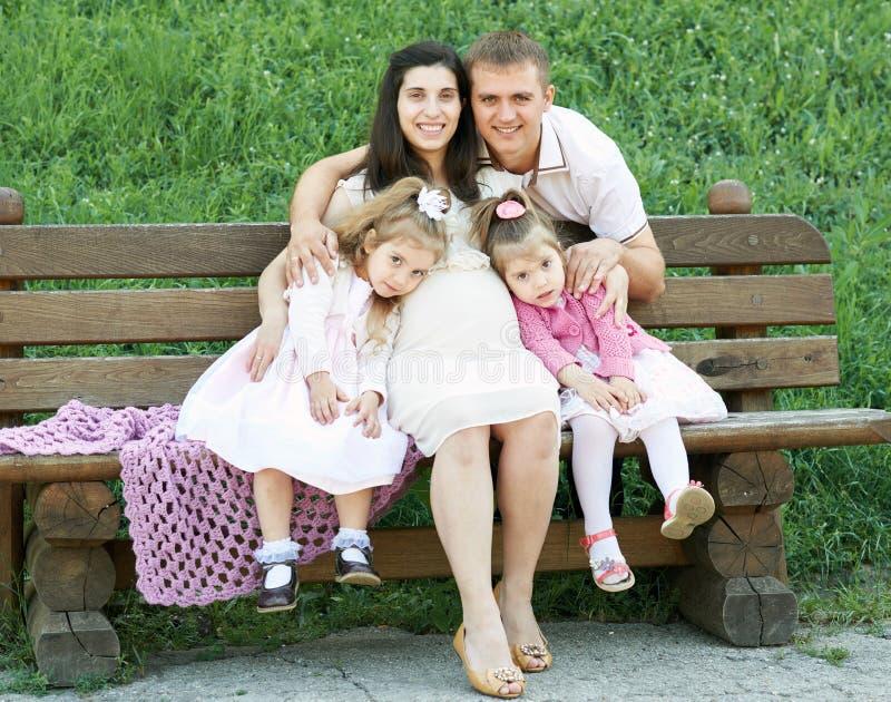 Familia feliz en la mujer al aire libre, embarazada del parque de la ciudad del verano, el padre y los niños, el día soleado bril fotos de archivo