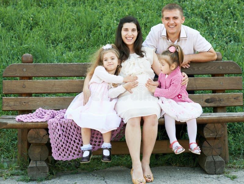 Familia feliz en la mujer al aire libre, embarazada del parque de la ciudad del verano, el padre y los niños, el día soleado bril foto de archivo