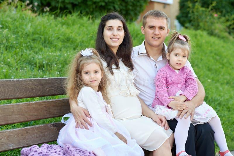 Familia feliz en la mujer al aire libre, embarazada del parque de la ciudad del verano, el padre y los niños, el día soleado bril foto de archivo libre de regalías