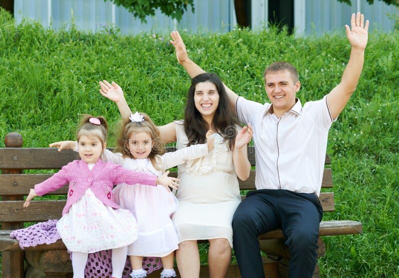 Familia feliz en la mujer al aire libre, embarazada del parque de la ciudad del verano, el padre y los niños, el día soleado bril imagenes de archivo