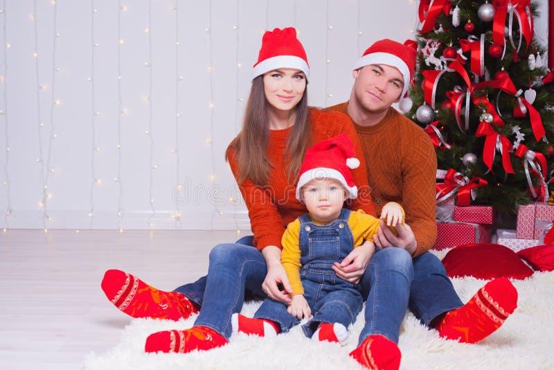 Familia feliz en la Nochebuena que se sienta junto cerca de árbol adornado foto de archivo