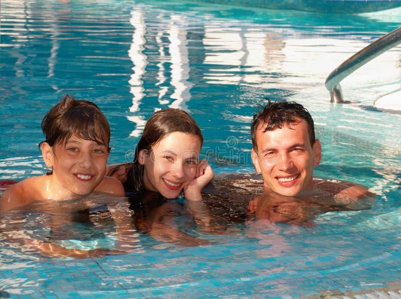 Familia feliz en la piscina foto de archivo