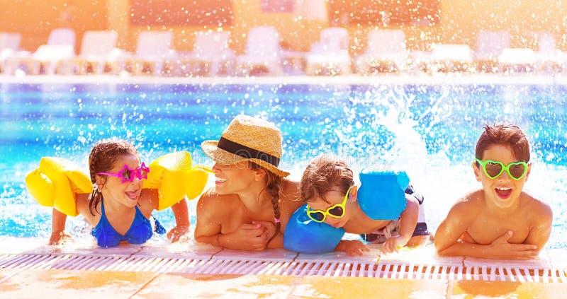 Familia feliz en la piscina fotos de archivo