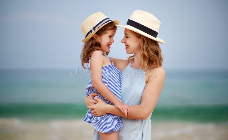 Familia feliz en la playa abrazo de la hija de la madre y del niño en el mar foto de archivo libre de regalías