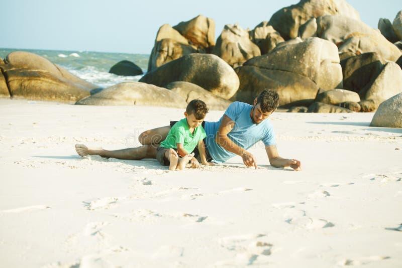 Familia feliz en la playa que juega, padre con la costa de mar del hijo que camina, rocas detr?s de vacaciones que toman sonrient fotos de archivo libres de regalías