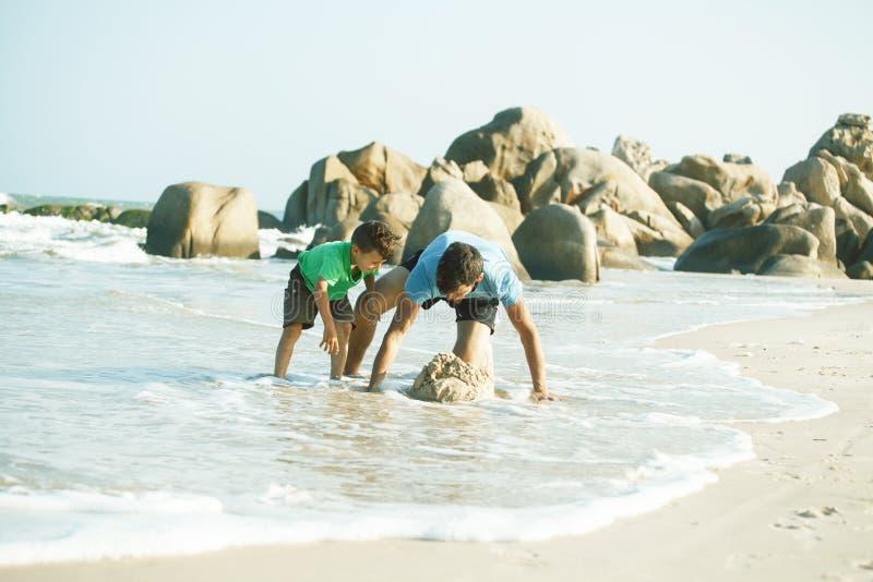 Familia feliz en la playa que juega, padre con la costa de mar del hijo que camina, rocas detr?s de vacaciones que toman sonrient imágenes de archivo libres de regalías