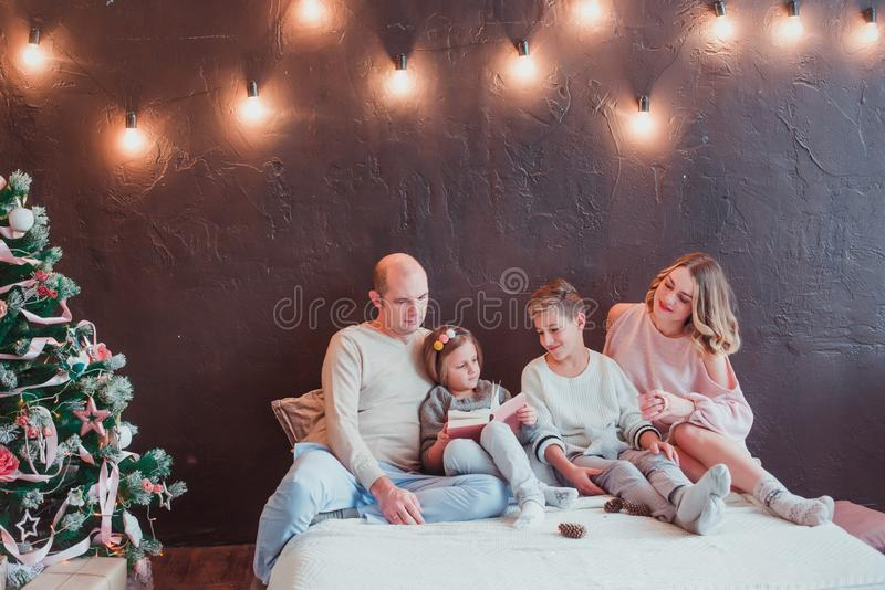 Familia feliz en la sentada interior del Año Nuevo en la cama y la lectura de un libro Están sonriendo está después un árbol de n imágenes de archivo libres de regalías