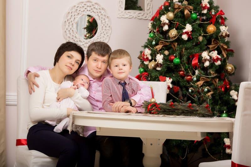 Familia feliz en la tabla del día de fiesta Árbol Navidad foto de archivo