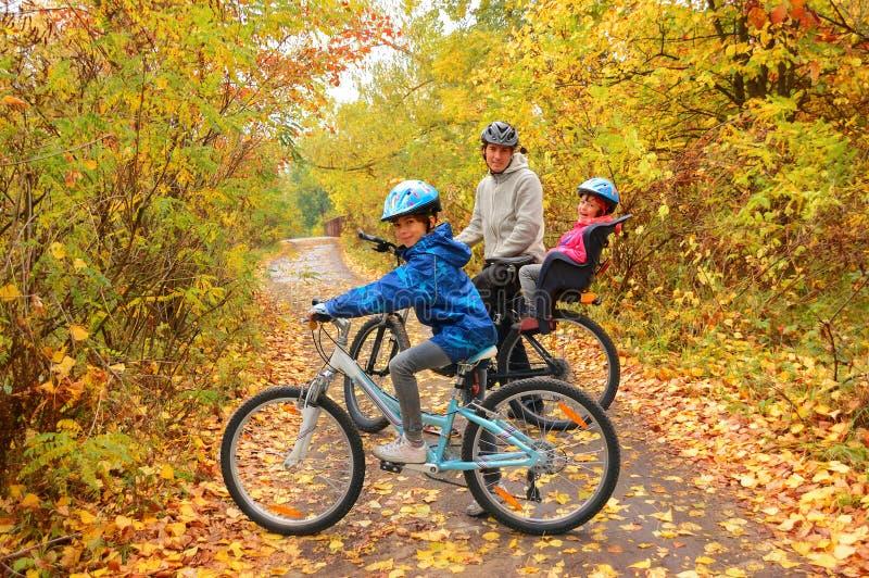 Familia feliz en las bicis en parque del otoño imagen de archivo