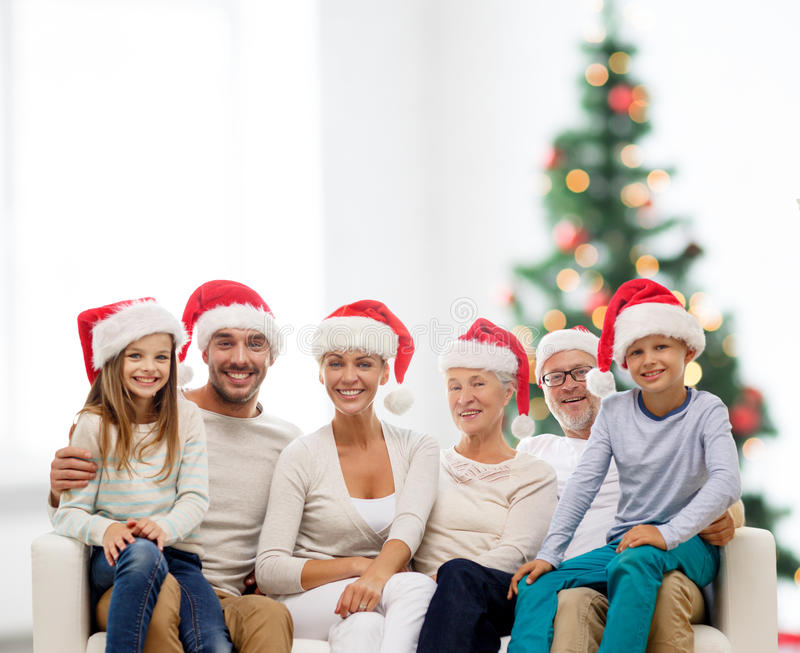 Familia feliz en los sombreros del ayudante de santa que se sientan en el sofá fotos de archivo