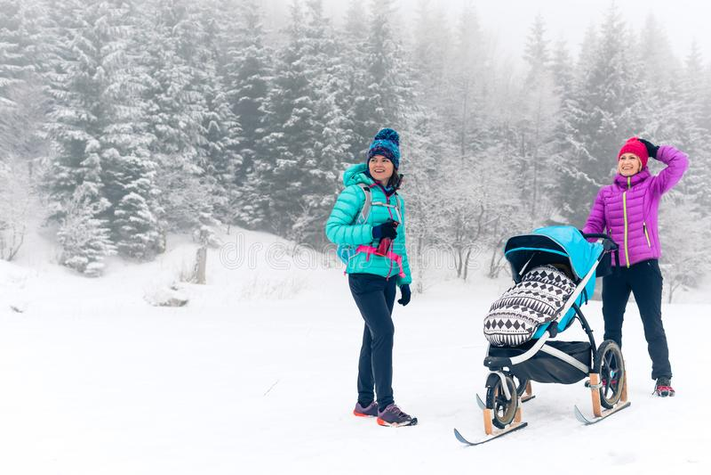 Familia feliz en montañas Madre con el cochecito de bebé que disfruta del MES imagen de archivo libre de regalías