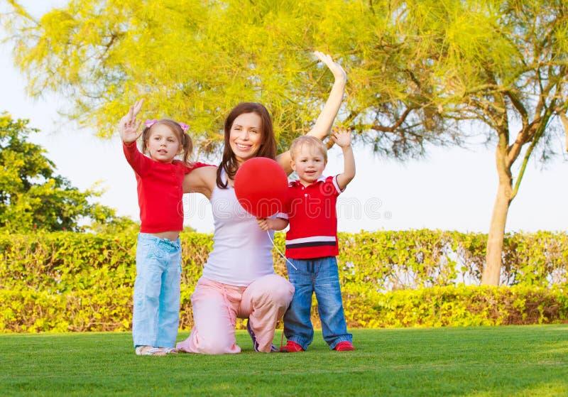 Familia feliz en parque de la primavera fotografía de archivo