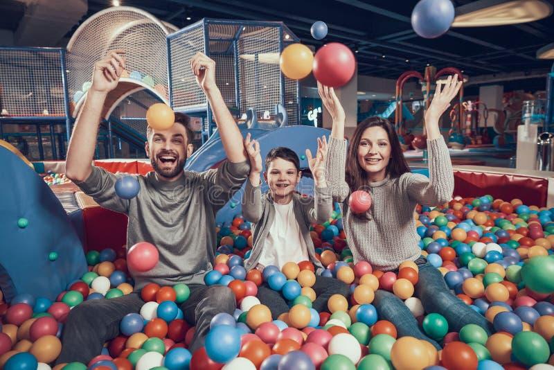 Familia feliz en piscina con las bolas fotos de archivo