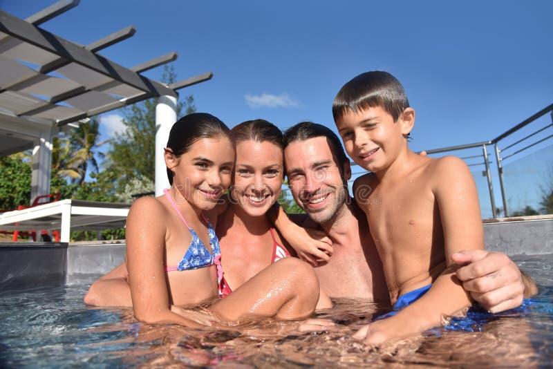 Familia feliz en piscina que disfruta de vacaciones de verano fotos de archivo libres de regalías