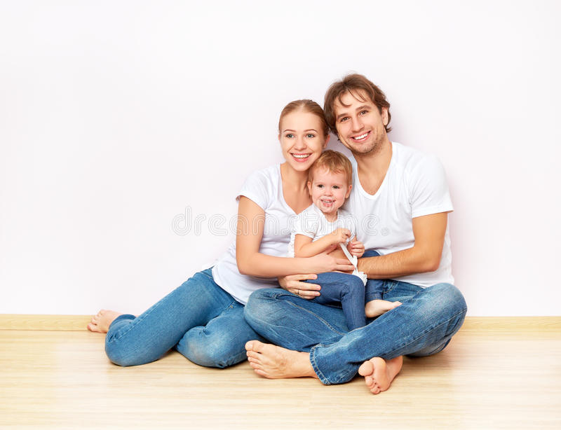 Familia feliz en piso cerca de la pared vacía en el apartamento comprado en hipoteca fotografía de archivo libre de regalías