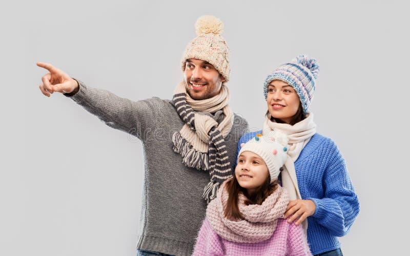 Familia feliz en ropa del invierno en fondo gris imagenes de archivo