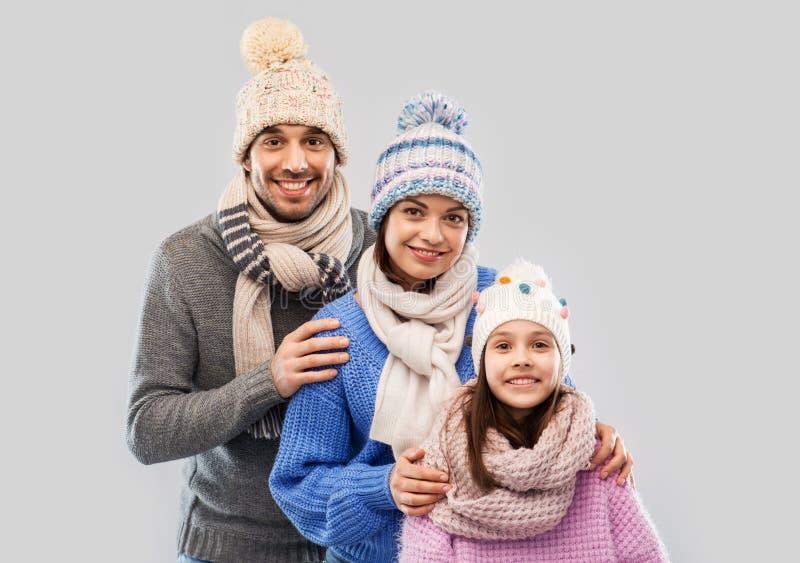 Familia feliz en ropa del invierno en fondo gris fotografía de archivo libre de regalías