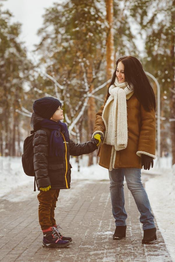 Familia feliz en ropa del invierno Niño pequeño que lleva a cabo la mano de su madre foto de archivo