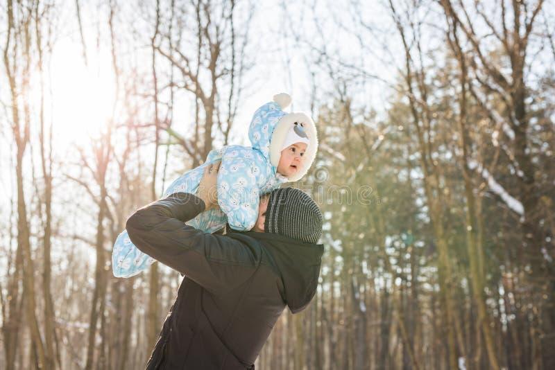 Familia feliz en un paseo del invierno en naturaleza El papá lanza para arriba al bebé fotos de archivo libres de regalías