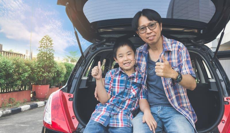 Familia feliz en un viaje por carretera, sentándose en el tronco del coche fotos de archivo libres de regalías