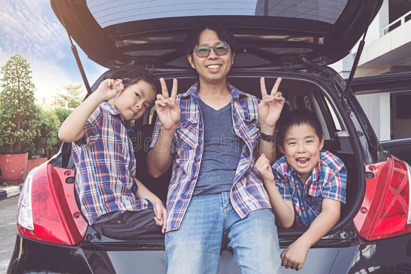 Familia feliz en un viaje por carretera, sentándose en el tronco del coche foto de archivo libre de regalías