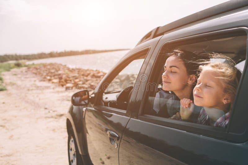 Familia feliz en un viaje por carretera en su coche El papá, la mamá y la hija están viajando por el mar o el océano o el río imagen de archivo