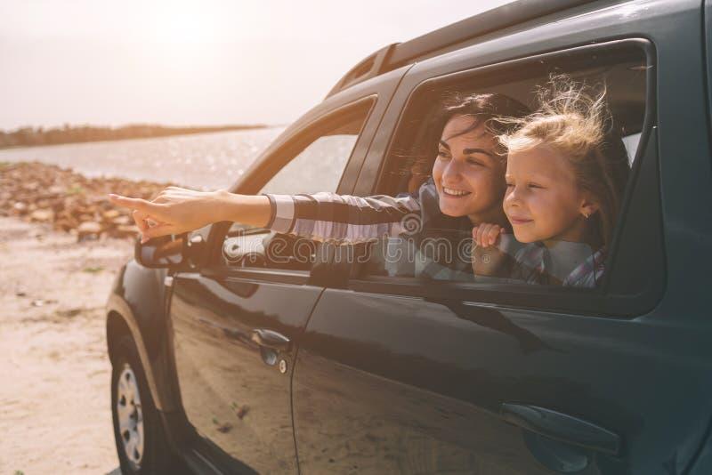 Familia feliz en un viaje por carretera en su coche El papá, la mamá y la hija están viajando por el mar o el océano o el río imagenes de archivo