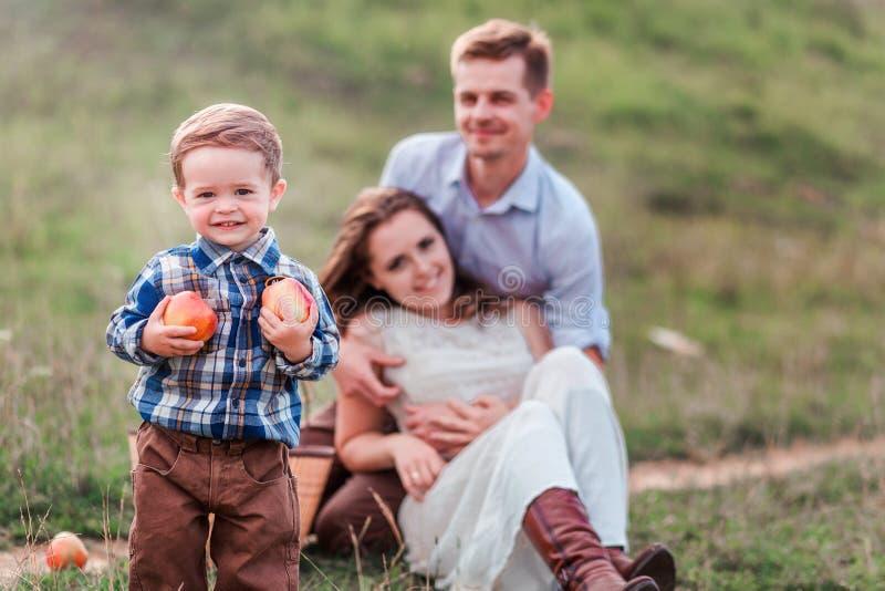 Familia feliz en una comida campestre Niño pequeño con las manzanas en el primero plano foto de archivo libre de regalías