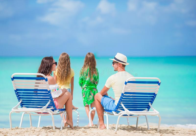 Familia feliz en una playa durante vacaciones de verano fotos de archivo