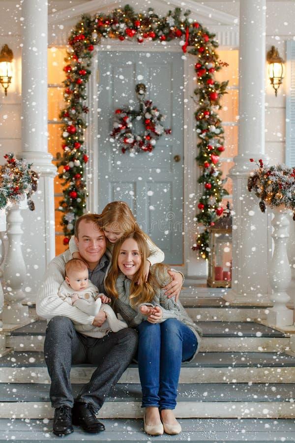 Familia feliz hermosa con las niñas en la sentada de punto del suéter fotografía de archivo