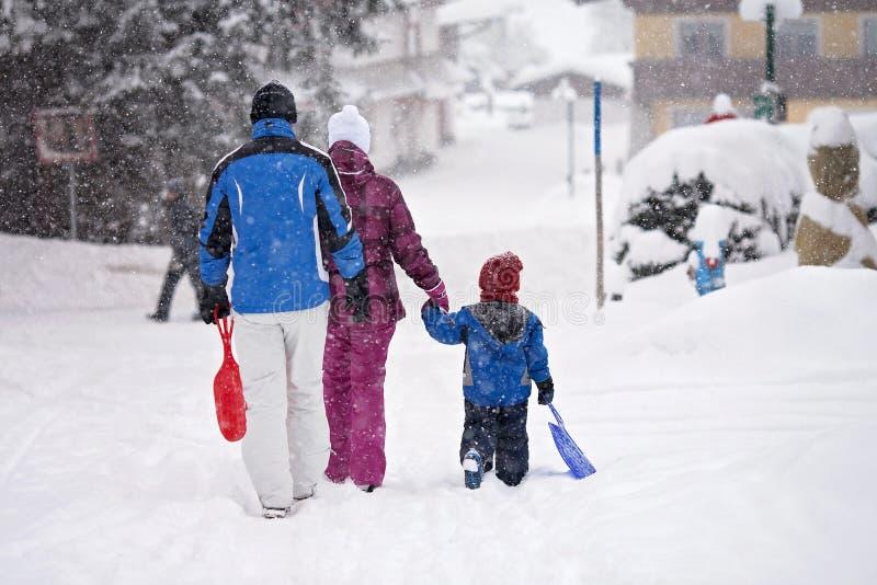 Familia feliz, invierno de salida a resbalar imagenes de archivo