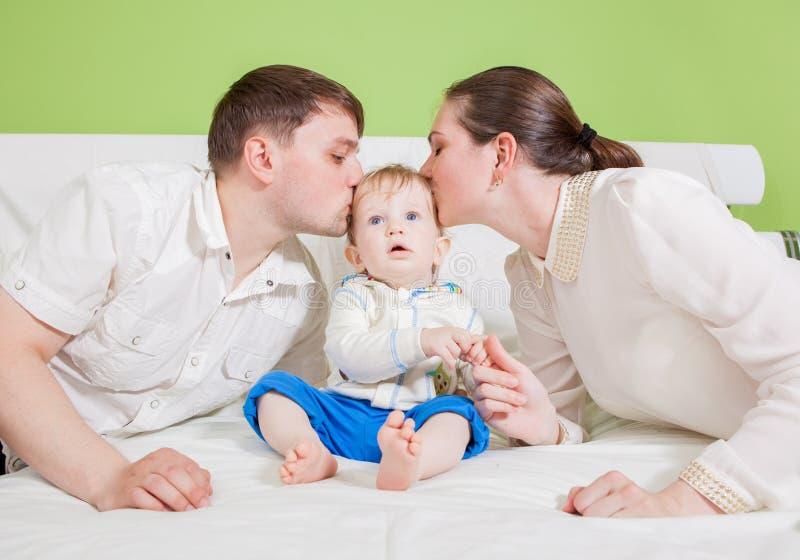 Familia feliz joven con el niño en casa imagen de archivo