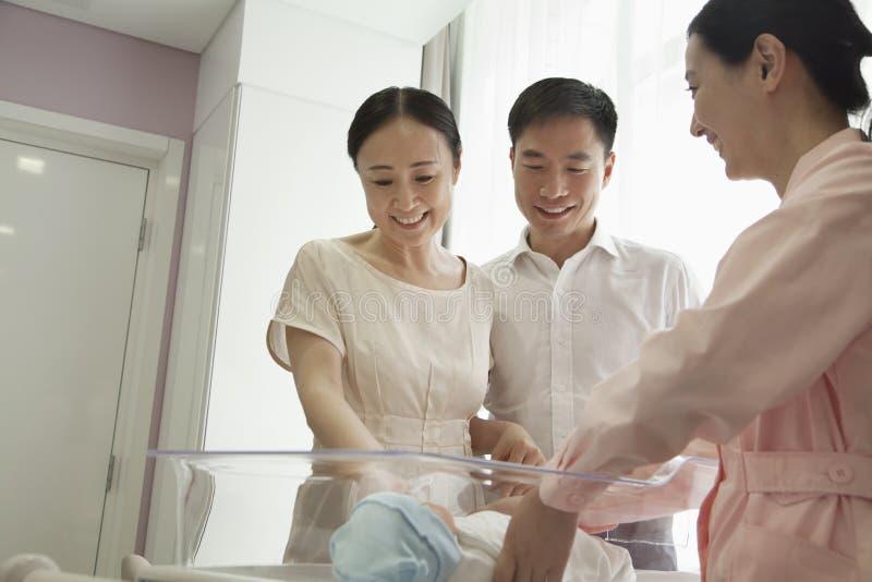 Familia feliz joven con la enfermera que mira abajo su recién nacido en el cuarto de niños del hospital fotos de archivo